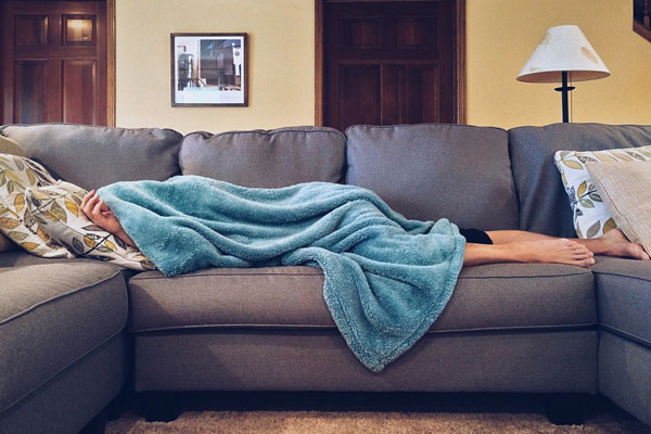 Woman lying under a blanket on the couch.