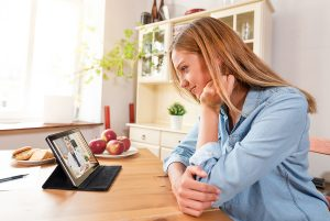 Woman sitting at her kitchen table consulting with a medical provider via her tablet