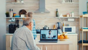 Senior couple during video conference with doctor using laptop in kitchen