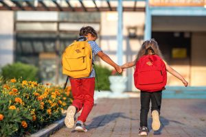 Picture of a brother and sister holding hands as they run to school.