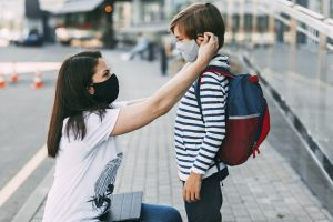 Picture of a mother adjusting her son's face mask before he goes to school.