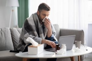 Picture of a sick man attending a telemedicine appointment using his laptop.
